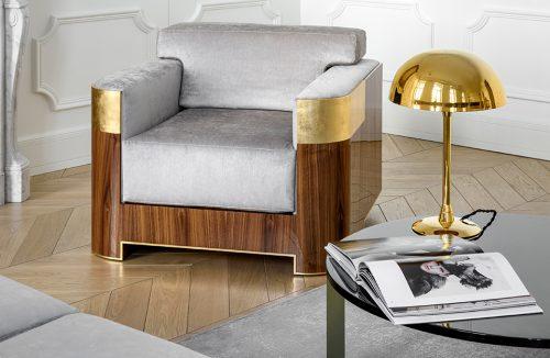 elegancki fotel od Atelier 1925 z szarym siedziskiem wykończony drewnem ze złotymi wstawkami obok okrągłego czarnego stolika ze złotą lampką