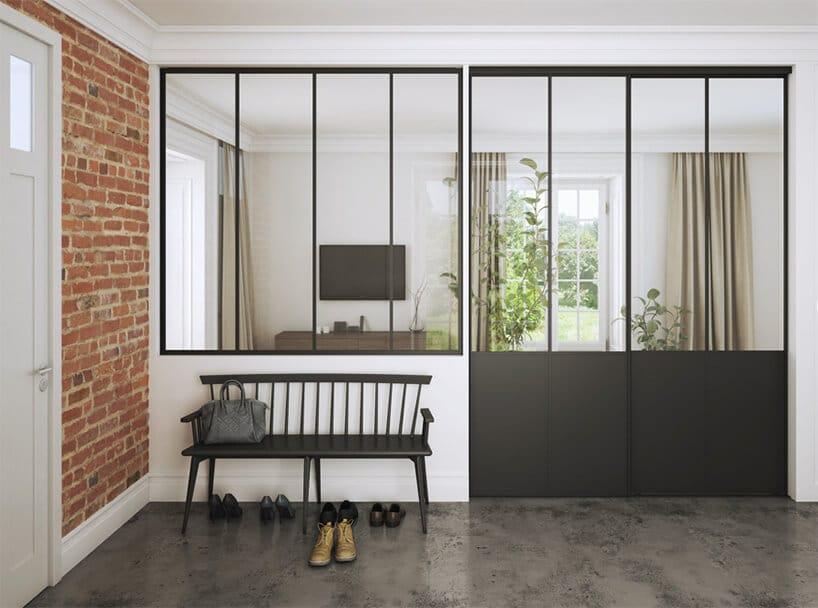 drewniana ławka przy białej iceglanej ścianie przy otwieranych szklanych drzwiach zmetalowymi wstawkami wkolorze szarym