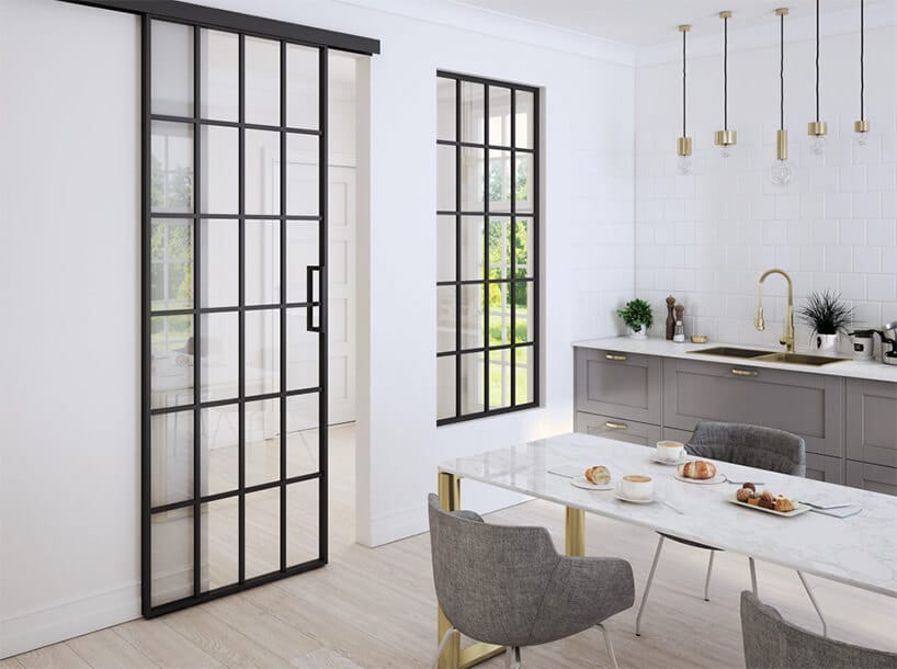 przeszklone drzwi przesuwne zczarnymi elementami konstrukcji wstylu loftowym wjasnym pomieszczeniu