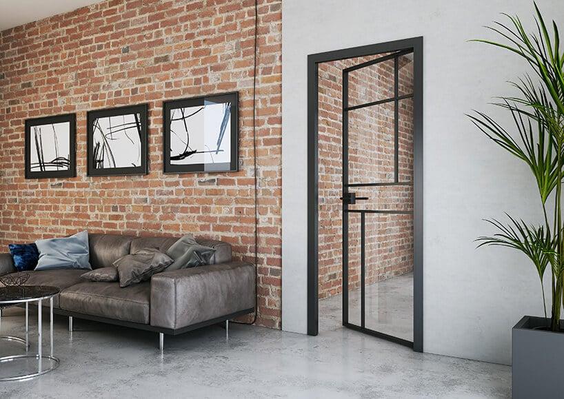 dwrz zpołączeniem szkła oraz metalowej czarnej konstrukcji na ścianie zstarej cegły ze srebrzystą kanapą oraz lustrami wramach