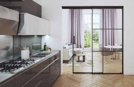 kuchnia z połyskującymi brązowymi frontami oraz białymi wiszącymi szafkami przy przesuwnych drzwiach ze szkła i metalowej ramki