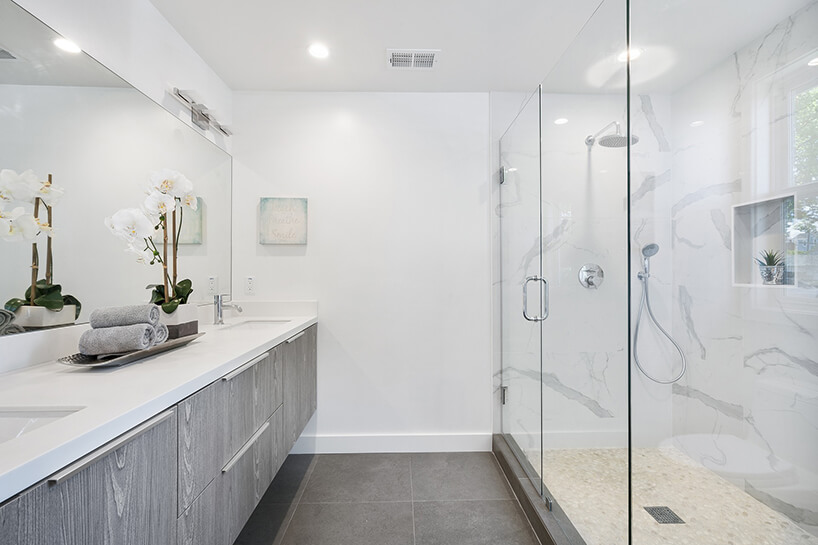 biała łazienka zdługim natryskiem za szklana ścianą na przeciwko podwieszonych szarych szafek zbiałym blatem