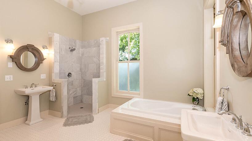 beżowa łazienka zczęsciowo zabudowanymi natryskiem obok stojącej umywalki iklasycznym stylu zniską zabudowaną wanną
