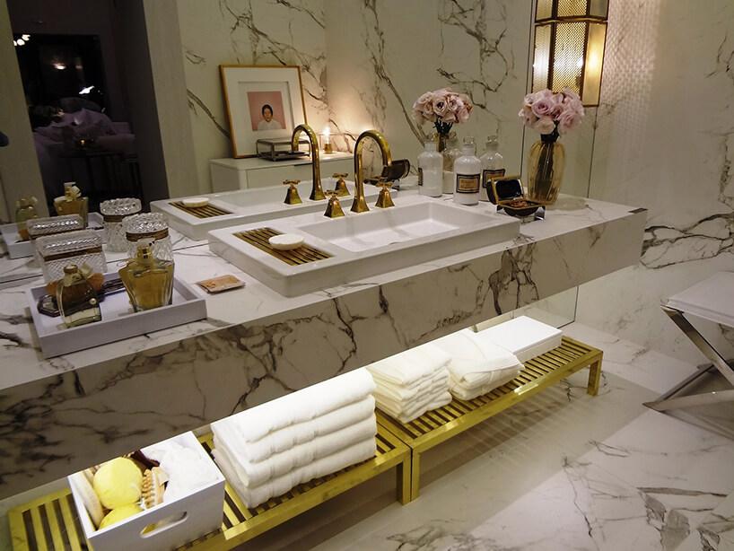 elegancka łazienka wykończona kaflami zkamiennym białym wzorem zelegancką umywalką ze złotą armaturą wstarym stylu