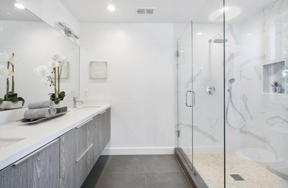 biała łazienka z długim natryskiem za szklana ścianą na przeciwko podwieszonych szarych szafek z białym blatem