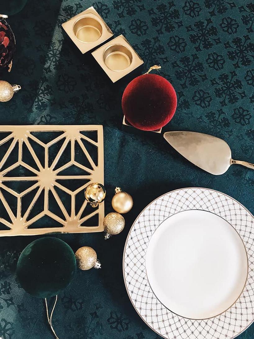biały talerz izłote ozdoby na ciemno zielonym obrusie