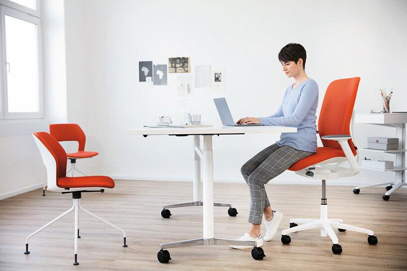 kobieta siedząca na biało czerwonym krześle AT od Wilkhahn przy nowoczesnym białym biurku