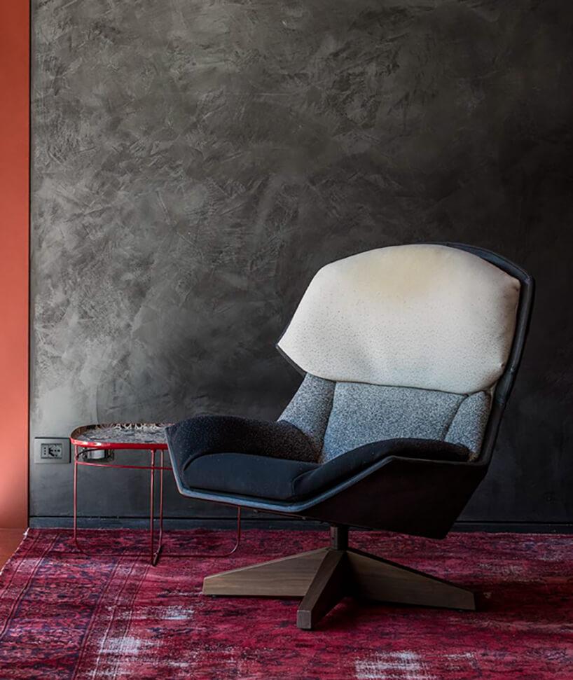 elegancki fotel Fotel Clarissa od Moroso zsiedziskiem wodcieniach niebieskiego koloru na różowym dywanie na tle szarej ściany