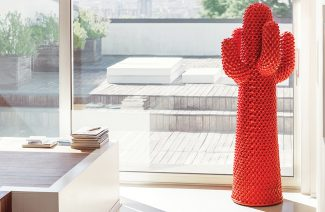 czerwony stojak Cactus od Gufram na tle drewnianego ciemnego tarasu
