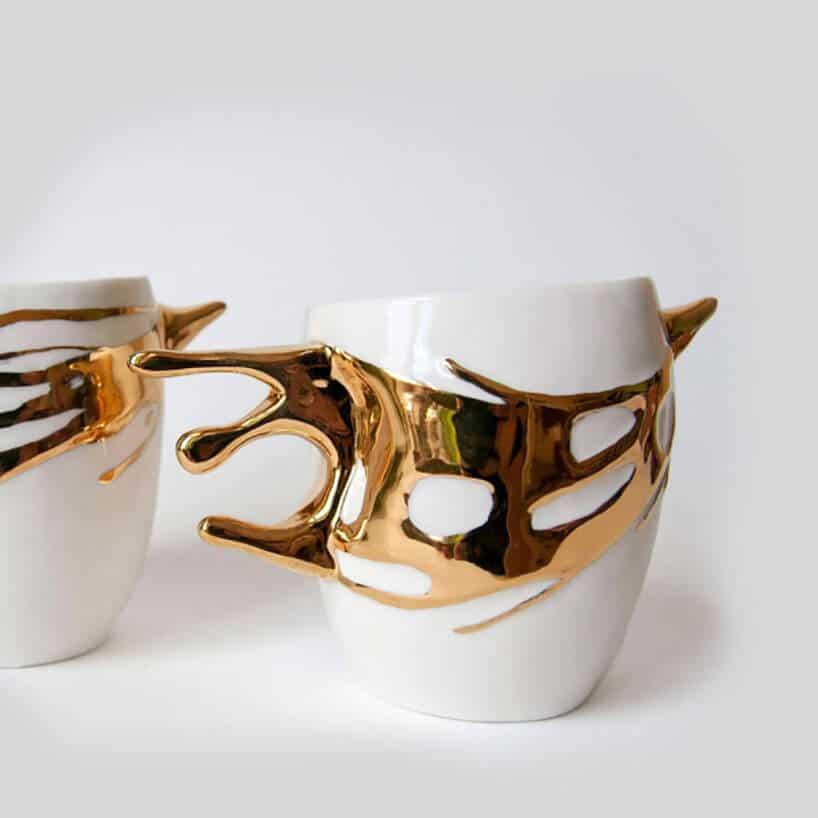 białe kubki zdobione złotem wnowej formie