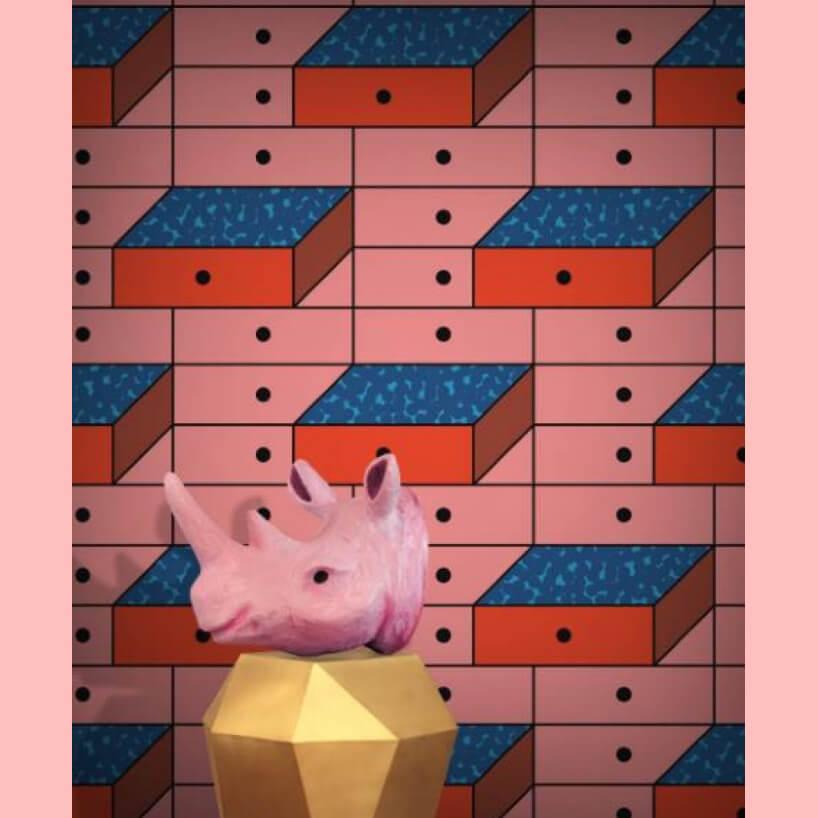 różowa tapeta Drawer wstylu pop art ściana szuflad jako tło dla różowej głowy nosorożca na złotym postumencie