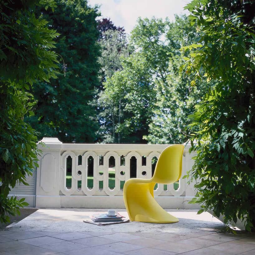 żółte krzesło Panton jednego plastikowego elementu na białym tarasie wpośród zieleni posiadłości