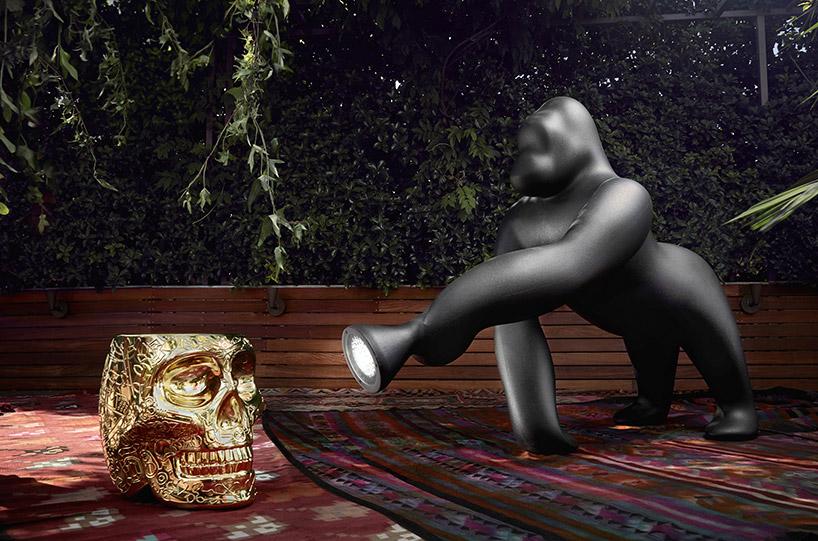 plastikowy czarny goryl jako lampa świecąca na złotą czaszkę