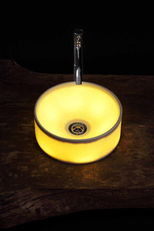 świecąca na żółto okrągła umywalka na drewnianym blacie