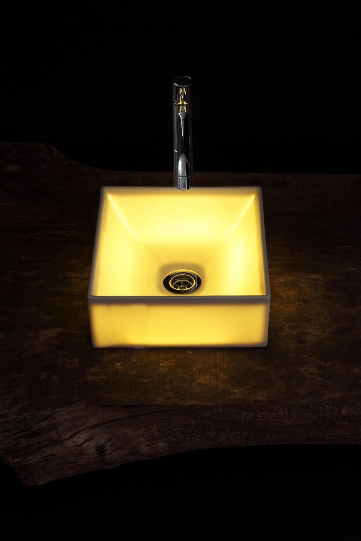 świecąca na żółto kwadratowa umywalka na drewnianym blacie