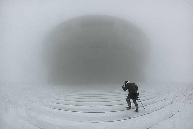 człowiek zmagający się zburzą śnieżną