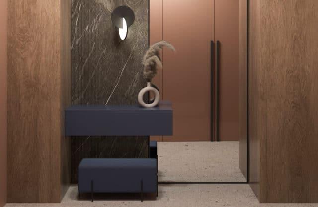 przedpokój z elementami drewnianymi wysokim lustrem oraz ciemną pufą