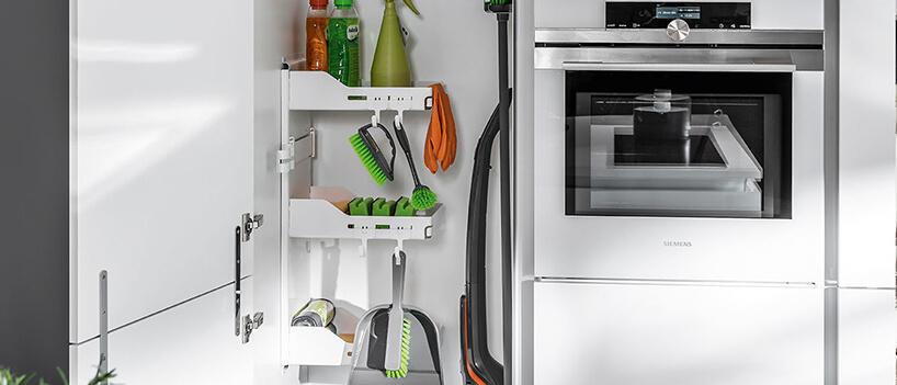 zestaw wyposażenia szafek PEKA Sesam wbiałej zabudowie obok białego piekarnika Siemens