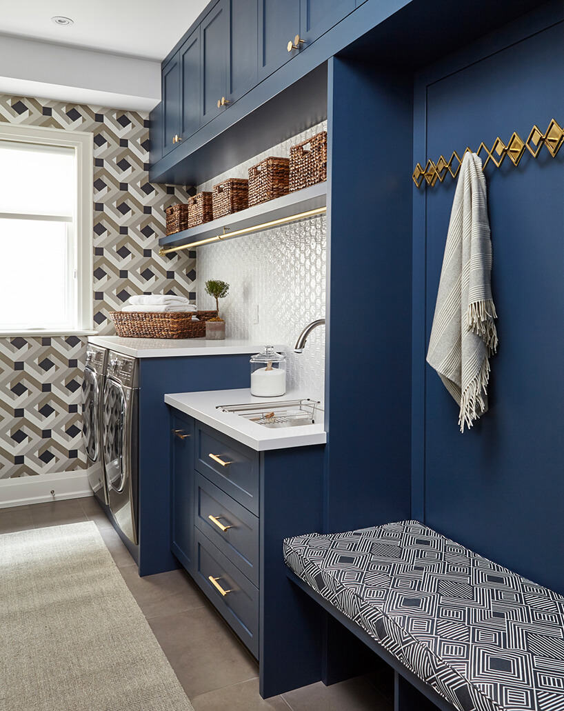 małe biało niebieskie pomieszczenie zdwoma srebrnymi urządzeniami do prania isuszenia