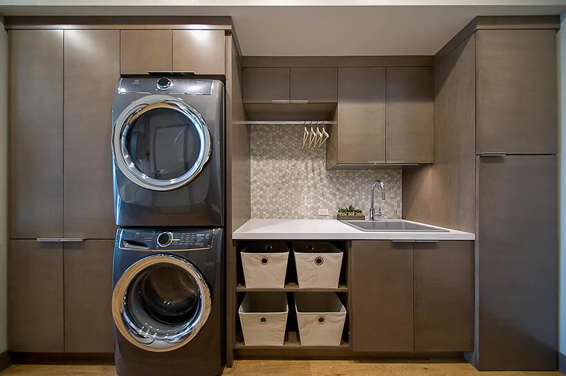 pralnia zbrązową zabudową ibłyszczącą pralką isuszarką