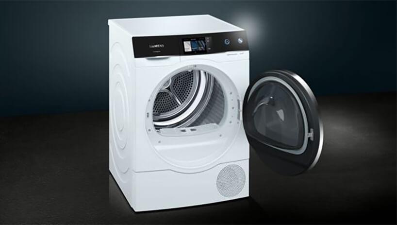 nowoczesna biało czarna suszarka do ubrań Siemens Avantgarde zotwartymi drzwiczkami