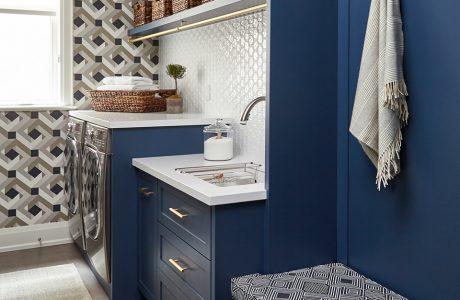 małe biało niebieskie pomieszczenie z dwoma srebrnymi urządzeniami do prania i suszenia