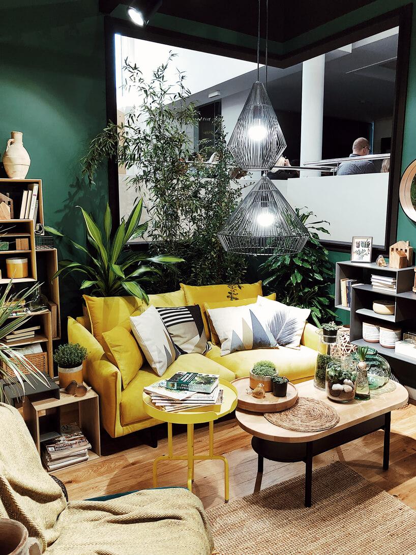 aranżacja salonu od VOX zżółtą sofą idużą ilością roślin