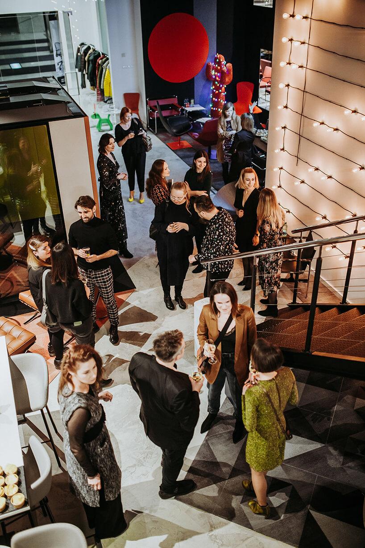 goście wshowroomie marki Aqina podczas prezentacji przy metalowych schodach