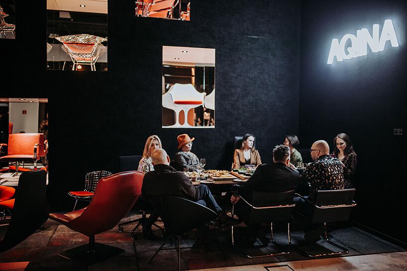goście przy dużym stole na tle ciemno niebieskiej ściany zneonem Aqina