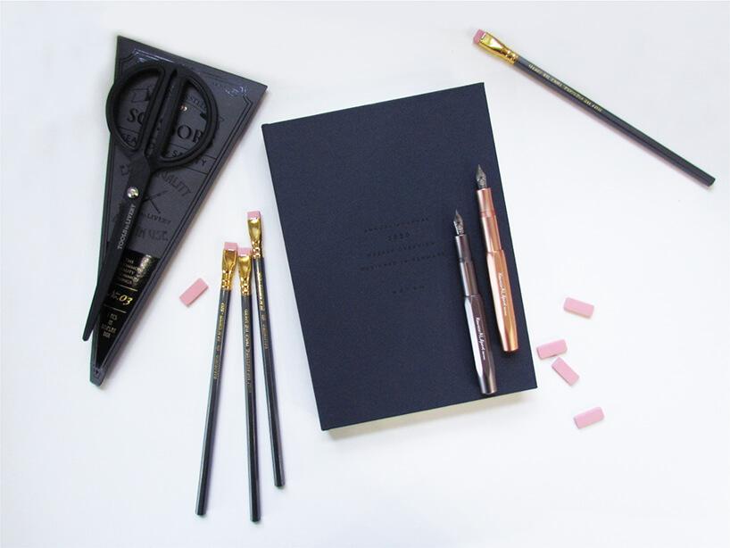 czarne nożyczki obok ołówków ipiór na kalendarzu osobistym lezące na białej powierzchni