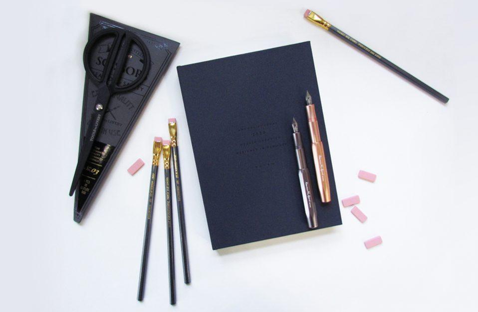 czarne nożyczki obok ołówków i piór na kalendarzu osobistym lezące na białej powierzchni