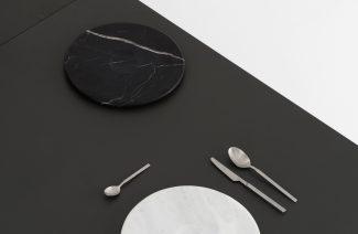 zestaw Moon Plate od Tre Product czarny i biały talerz z 3 sztućcami na czarnym blacie