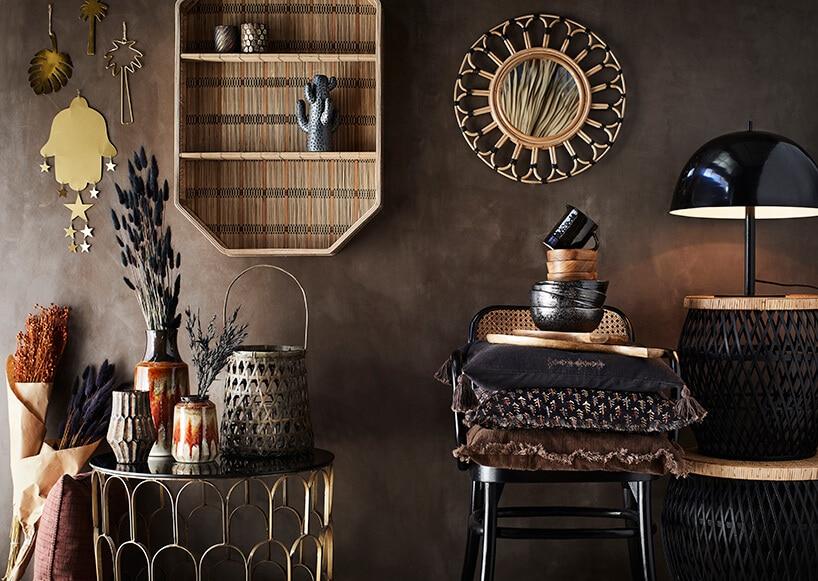 ciemne pomieszczenie zbrązową ścianą oraz brązowymi ciemnymi dodatkami wformie krzesła
