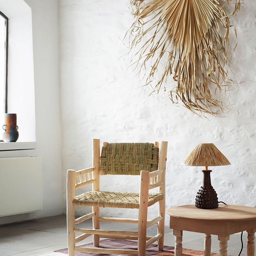 krzesło drewniane zzielonymi materiałem przy biało szarej ścianie