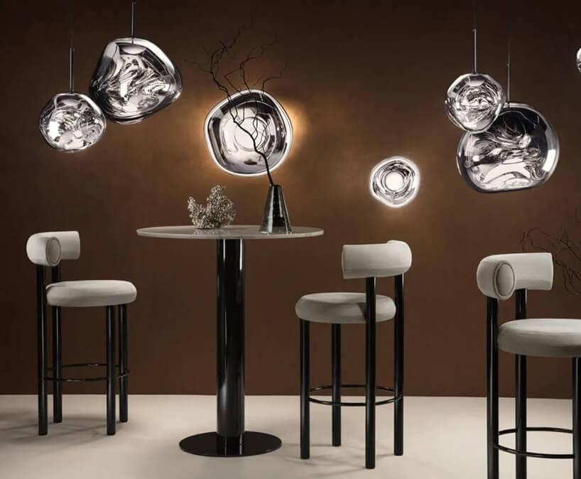 Lampy na tle brązowej ściany ze stolikami ikrzesłami wkoło