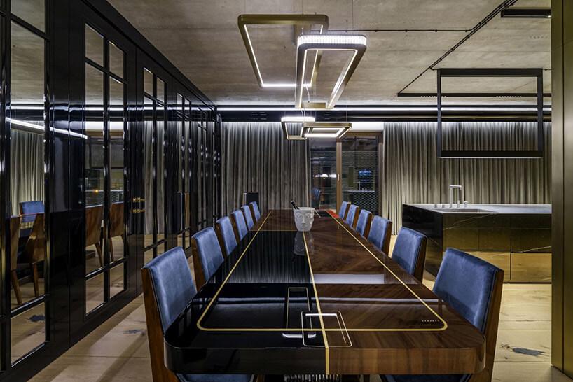 niebieskie krzesła przy długim czarnym stole obradowym
