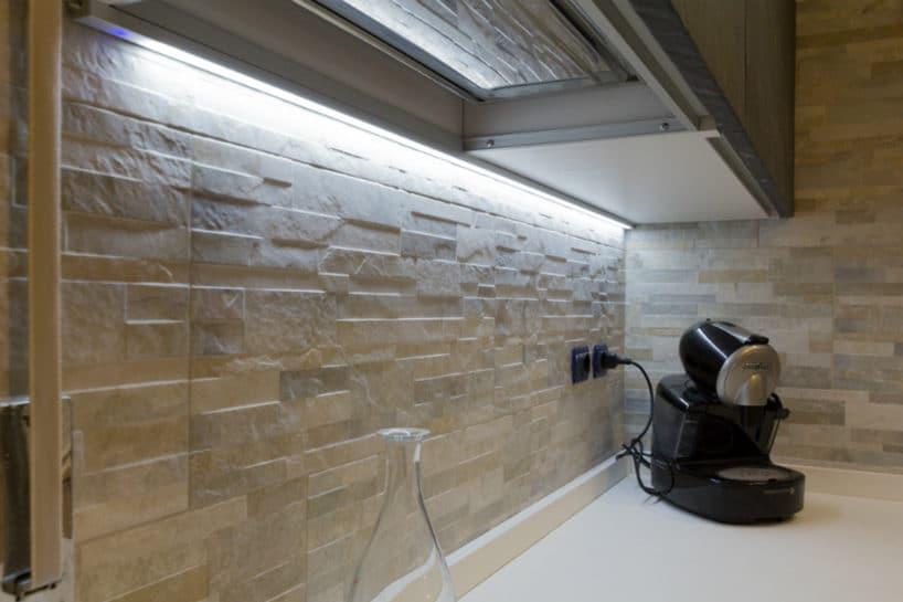 panel led pod szafką kuchenną świecący na przestrzenną płytkę kamienną