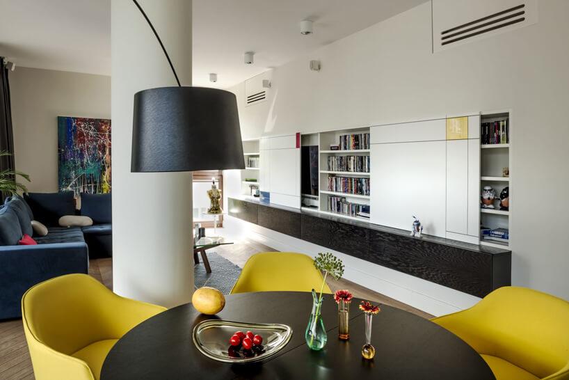czarny stół zżółtymi krzesłami na tle białego apartamentu zczarnym wstawkami