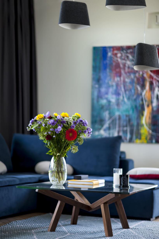 mały szklany stolik ndrewnianych nogach na tle niebieskiej sofy