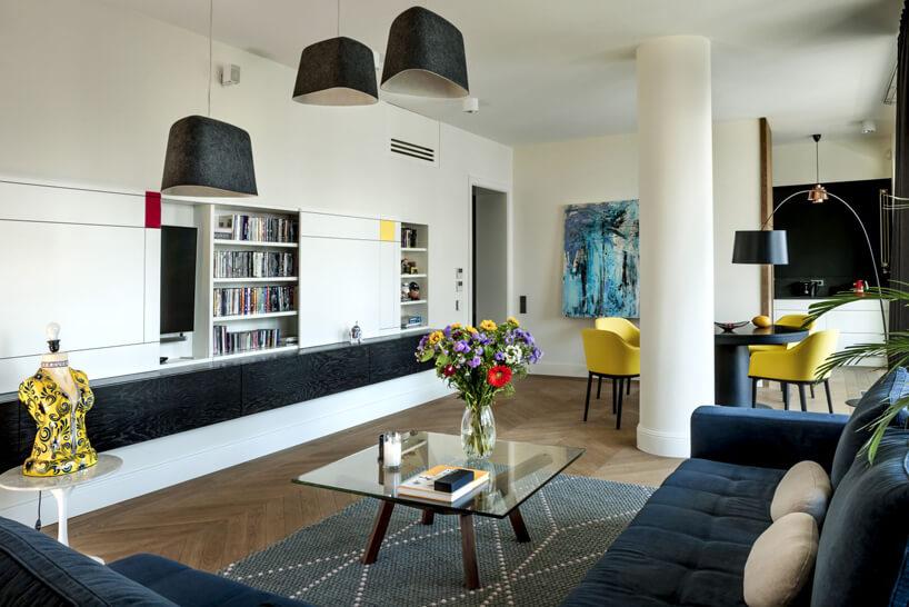 mały kwadratowy szklany stolik obok niebieskiej sofy na tle białego apartamentu zczarnym wstawkami