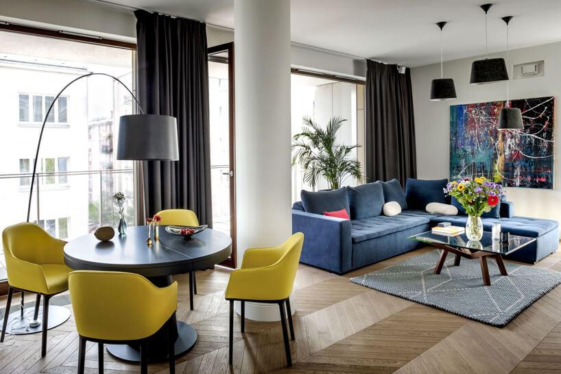 ciemny okrągły stół zczterema żółtymi krzesłami obok niebieskiej sofy