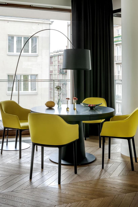 ciemny okrągły stół zczterema żółtymi krzesłami pod wisząco-stojącą lampą