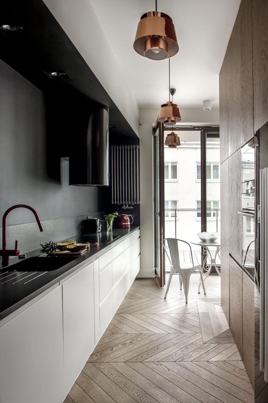 kuchnia zciemny blatem iścianą nad białym szafkami
