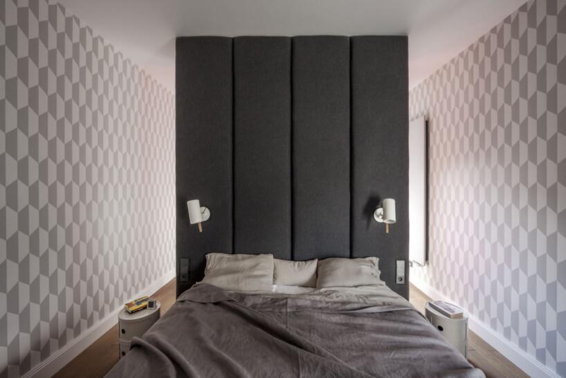 duże łóżko na pod ścianą obitą szarym materiałem