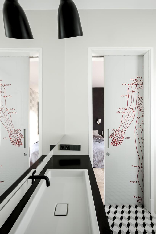drzwi zczerwoną grafiką wbiało-czarnej łazience