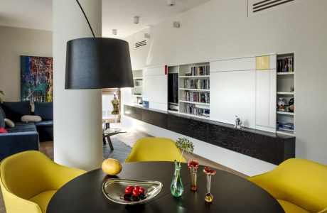 czarny okrągły stół z żółtymi krzesłami na tle białego apartamentu z czarnym wstawkami