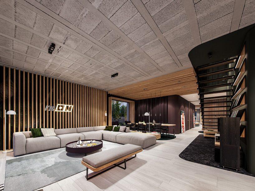 projekt nowoczesnego wnętrza domu od Zarysy salon zjasną podłoga isufitem zdużą modułową sofą na tle ściany zdrewnianym wykończeniem