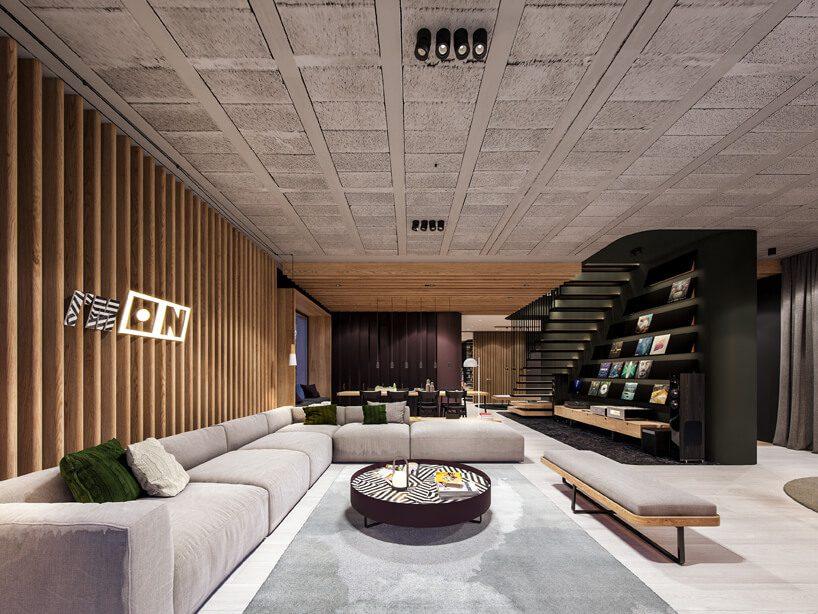 projekt nowoczesnego wnętrza domu od Zarysy salon zdużą modułową sofą obok czarnej ściany ze schodami izabudowanymi półkami