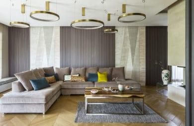 złote kręgi na suficie w formie lamp oraz rogowa szara kanapa z poduszkami w kolorze żółtym ciemno szarym i beżowym w salonie z naturalną podłogą