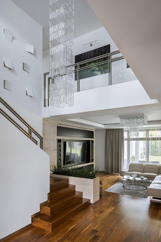 białe wnętrze domu zdrewnianą podłogą zdrewnianym schodami ze złota metalową poręczą